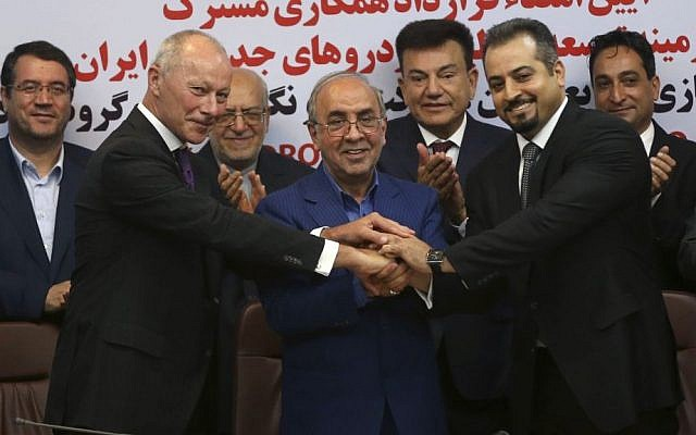 Chief Competitive Officer of Groupe Renault Thierry Bolloré, left, Chairman of Industrial Development and Renovation Organization of Iran, IDRO, Mansour Moazami, center, and Negin Group CEO Kourosh Morshed Solouk join hands after signing a deal in Tehran, Iran, Monday, Aug. 7, 2017. (AP Photo/Vahid Salemi)