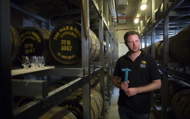 In this Thursday, Aug. 10, 2017 photo, Israeli Eitan Attir is seen in the barrels room at the 'Milk and Honey' whiskey distillery in Tel Aviv, Israel. (AP Photo/Sebastian Scheiner)