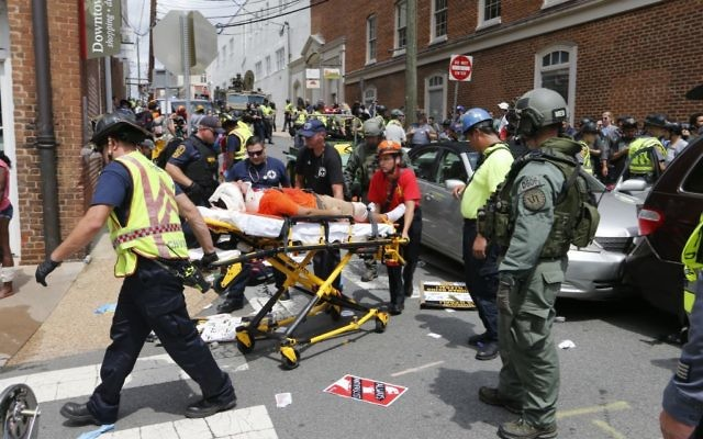 Rescue personnel help injured people after a car ran into a large group of protesters after a white nationalist rally in Charlottesville, Virginia, August 12, 2017.(AP Photo/Steve Helber)