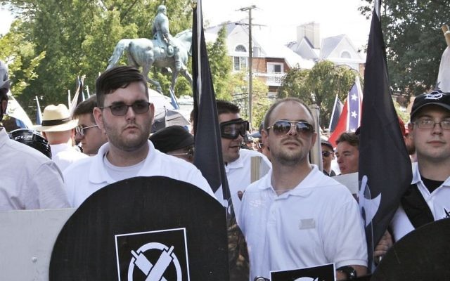 In this Saturday, August 12, 2017 photo, James Alex Fields Jr., second from left, holds a black shield in Charlottesville, Virginia, where a white supremacist rally took place. Fields was later charged with second-degree murder and other counts after authorities say he plowed a car into a crowd of people protesting the white nationalist rally. (Alan Goffinski via AP)