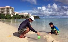 Kenji Kikuchi plays with his son Hideki in Ypao Beach, Tumon, Guam Monday, Aug. 14 2017. (AP Photo/Grace Bordallo)