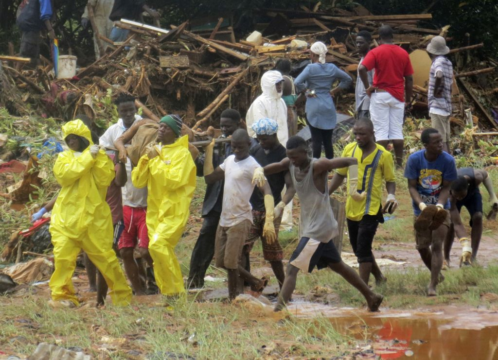Rescue workers carry the body of a victim from the site of a mudslide in Regent, east of Freetown, Sierra Leone, Monday, August 14, 2017. (AP/ Manika Kamara)