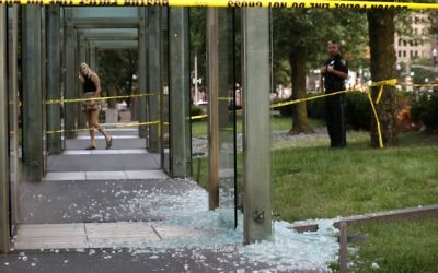 A passerby, left, and a law enforcement official, right, stand near broken glass at the New England Holocaust Memorial on Monday, Aug. 14, 2017, in Boston.  (AP/Steven Senne)