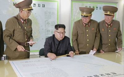 This image made from video of an Aug. 14, 2017, still image broadcast in a news bulletin on Tuesday, Aug. 15, 2017, by North Korea's KRT shows North Korean leader Kim Jong Un receiving a briefing in Pyongyang.(KRT via AP Video)