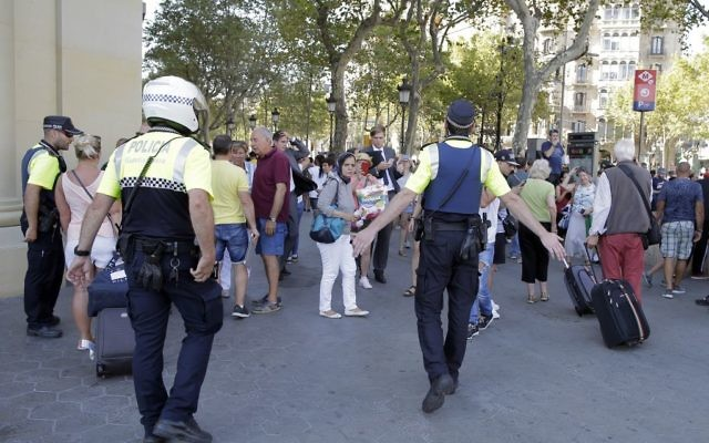 Police officers tell members of the public to leave the scene of a terror attack in a street in Barcelona, Spain, Thursday, Aug. 17, 2017. (AP Photo/Manu Fernandez)