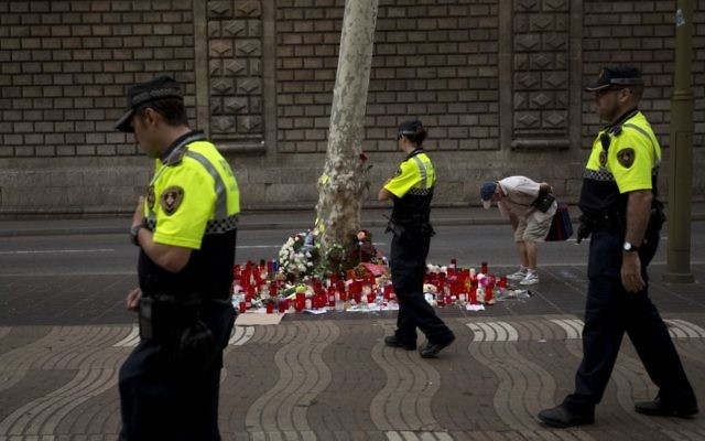 Spanish police officers walk past candles and flowers placed on the ground after a terror attack that killed 14 people and wounded over 120 in Barcelona, Spain,  August 20, 2017. (AP/Emilio Morenatti)