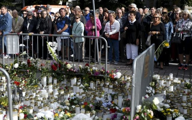 A minute's silence for the victims of a stabbing attack is held at Turku Market Square in Turku, Finland, August 20, 2017. (Vesa Moilanen/Lehtikuva via AP)