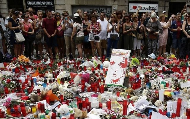 People stand next to candles and flowers placed on the ground after a terror attack that killed 14 people and wounded over 120 in Barcelona, Spain, Sunday, Aug. 20, 2017. (AP Photo/Manu Fernandez)