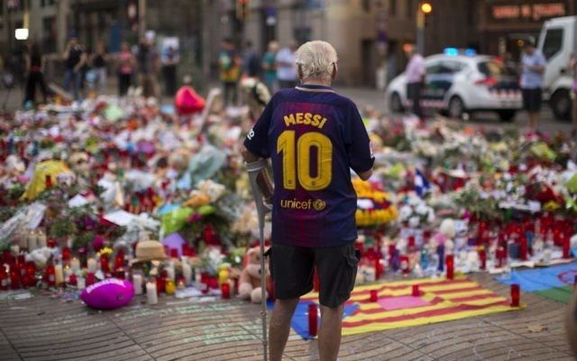 A man stands next to flags, flowers, messages and candles to the victims on Barcelona's historic Las Ramblas promenade. (AP /Emilio Morenatti)