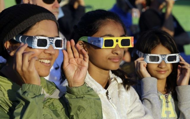 Schweta Kulkarni, from left, Rhea Kulkarni and Saanvi Kulkarni, from Seattle, try out their eclipse glasses on the sun at a gathering of eclipse viewers in Salem, Ore., early Monday, Aug. 21, 2017. (AP/Don Ryan)