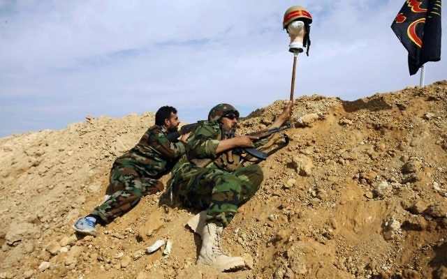 In this Nov. 22, 2013 file photo, Iraqi and Lebanese Shiite fighters from a group called the Hussein Brigade use a helmet to draw sniper fire, during clashes with the Sunni-dominated Free Syrian Army, in the town of Hejeira, near Damascus, Syria. (AP Photo/Jaber al-Helo, File)