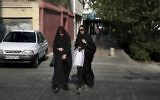 """In this Thursday, Aug. 24, 2017, photo, two Iranian women cross a street while wearing the """"chador,"""" a head-to-toe garment, in downtown Tehran, Iran. (AP Photo/Vahid Salemi)"""