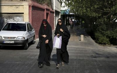 "In this Thursday, Aug. 24, 2017, photo, two Iranian women cross a street while wearing the ""chador,"" a head-to-toe garment, in downtown Tehran, Iran. (AP Photo/Vahid Salemi)"