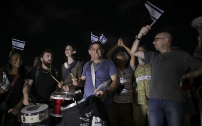 Menny Naftali center, and Eldad Yaniv, far right, main organizers of a weekly protest against Prime Minister Benjamin Netanyahu, in front of the home of Attorney General Avichai Mandelblit in Petah Tikva, August 26, 2017.  (AP Photo/Dan Balilty)