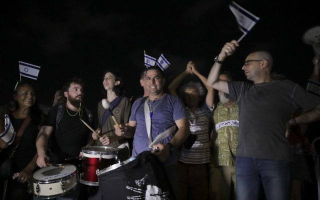 Menny Naftali, center, and Eldad Yaniv, far right, the main organizers of a weekly protest against Prime Minister Benjamin Netanyahu, in front of the home of Attorney General Avichai Mandelblit in Petah Tikva, August 26, 2017.  (AP Photo/Dan Balilty)