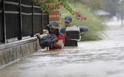Residents wade through floodwaters from Tropical Storm Harvey, August 27, 2017, in Houston, Texas. (AP Photo/David J. Phillip)