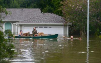 A family evacuates their Meyerland home in Houston, August 27, 2017. (Mark Mulligan/Houston Chronicle via AP)