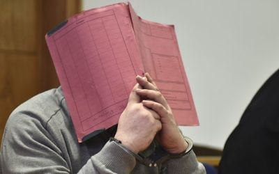 In this Feb. 26, 2015 photo former nurse Niels Hoegel., accused of multiple murder and attempted murder of patients, covering his face with a file at the district court in Oldenburg, Germany.  (Carmen Jaspersen/dpa via AP)