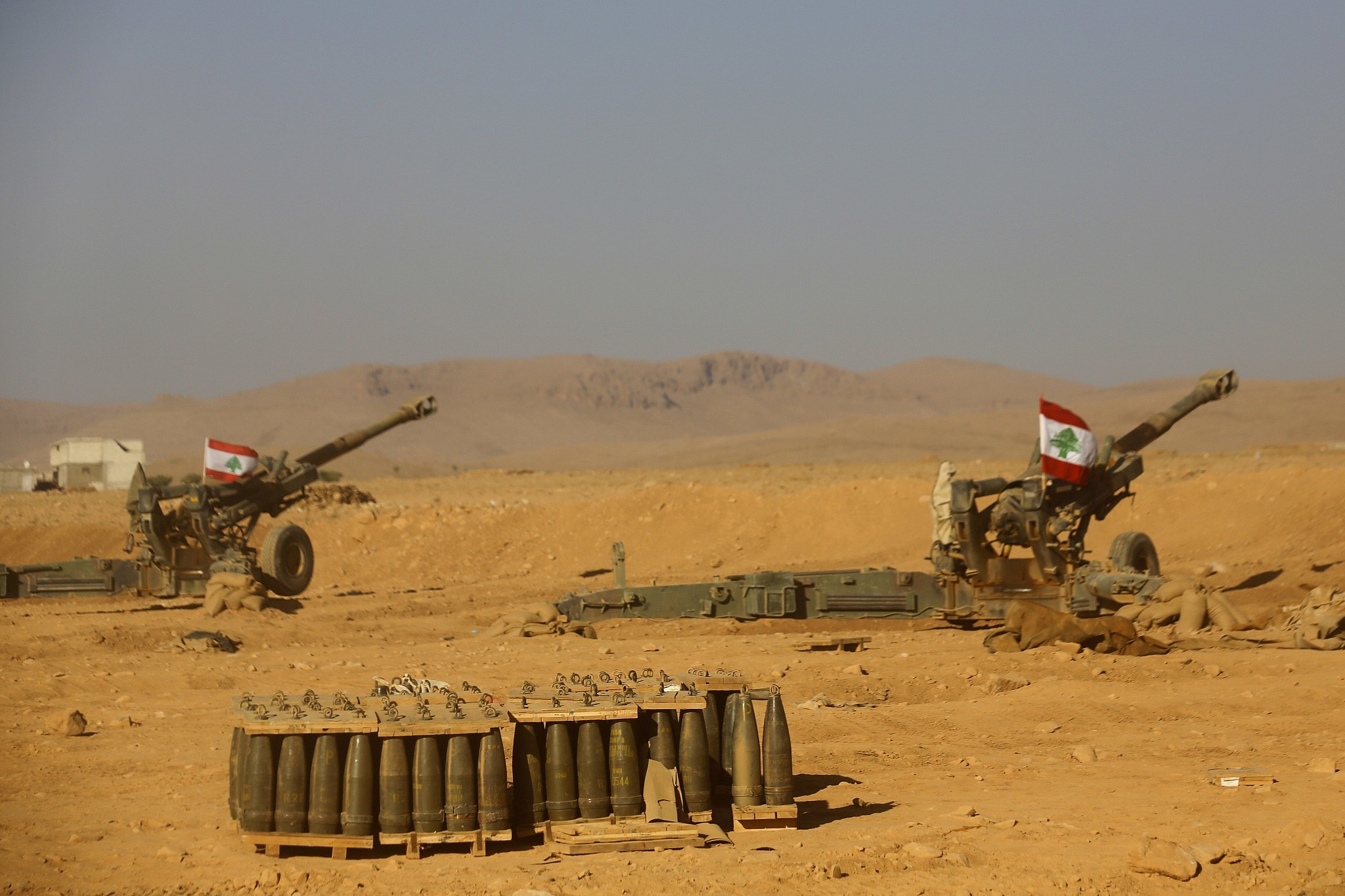 Lebanese national flags are set on the top of cannons inside a base during a media trip organized by the Lebanese army, on the outskirts of Ras Baalbek, northeast Lebanon, Monday, Aug. 28, 2017. Lebanon's Hezbollah TV is reporting that Islamic State militants started leaving the border area with Syria on Monday as part of a negotiated deal to end the extremist group's presence there. (AP Photo/Hassan Ammar)