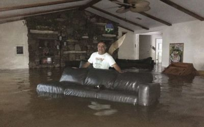 This Sunday, August 27, 2017, photo provided by Ramit Plushnick-Masti, shows her husband, Rafi, standing in waist-high water inside their flooded home in Houston's Meyerland neighborhood that was caused by Tropical Storm Harvey.  (Ramit Plushnick-Masti via AP)