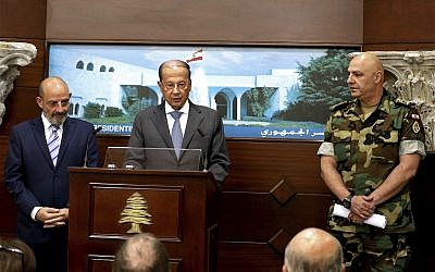 In this photo released by Lebanon's official government photographer Dalati Nohra, Lebanese Army Commander Gen. Joseph Aoun, right, and Spanish Defense Minister Yacoub Sarraf, left, listen to Lebanese President Michel Aoun, speaking to journalists at the Presidential Palace in Baabda, east of Beirut, Lebanon, Wednesday, Aug. 30, 2017. (Dalati Nohra via AP)