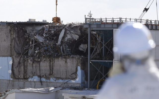 In this Feb. 10, 2016 file photo, a member of the media tour group wearing a protective suit and a mask looks at the No. 3 reactor building at Tokyo Electric Power Co's (TEPCO) tsunami-crippled Fukushima Dai-ichi nuclear power plant in Okuma, Fukushima Prefecture, northeastern Japan. (Toru Hanai/Pool Photo via AP, File)
