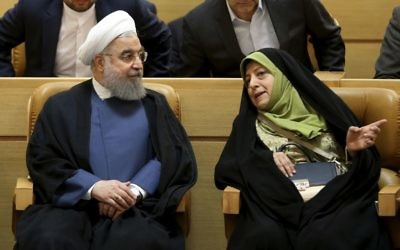 Iranian President Hassan Rouhani, left, listens to the Vice-President in charge of environmental affairs Masoomeh Ebtekar while attending a conference on combating sand and dust storms, in Tehran, Iran, Monday, July 3, 2017 (AP Photo/Vahid Salemi)