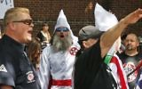 Members of the KKK are escorted by police past a large group of protesters during a KKK rally Saturday, July 8, 2017, in Charlottesville, Va. (AP Photo/Steve Helber)