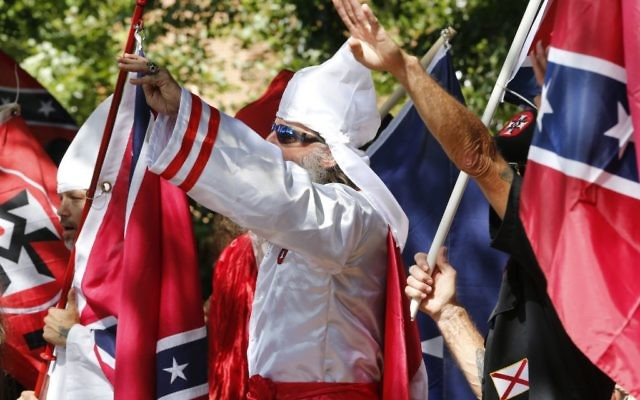 Klan members salute during a KKK rally in Justice Park Saturday, July 8, 2017, in Charlottesville, Va. (AP Photo/Steve Helber)