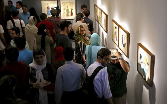 "Iranians look at paintings of Narges Mousavi in ""House of Free Designers"" art gallery in Tehran, Iran, Friday, Aug. 11, 2017. (Ebrahim Noroozi/AP)"
