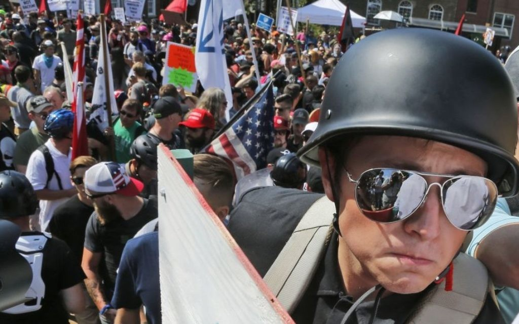 A white nationalist demonstrator with a helmet and shield walks into Lee Park in Charlottesville, Virginia. Hundreds of people chanted, threw punches, hurled water bottles and unleashed chemical sprays on each other, after violence erupted at a white nationalist rally in Virginia, on August 12, 2017. (AP Photo/Steve Helber)