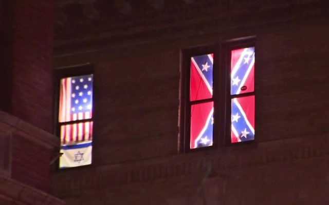 This Aug. 17, 2017 image from video shows a Confederate flag, right, displayed alongside an Israeli flag and a colonial-era American one in the seventh-floor windows of an apartment in the East Village neighborhood of New York. (PIX11 News via AP)
