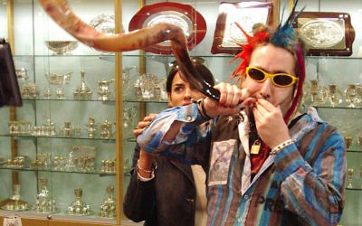 Bram Presser of the band Yidcore blowing a shofar at a Judaica store in Melbourne, Australia. (Peter Haskin/via JTA)