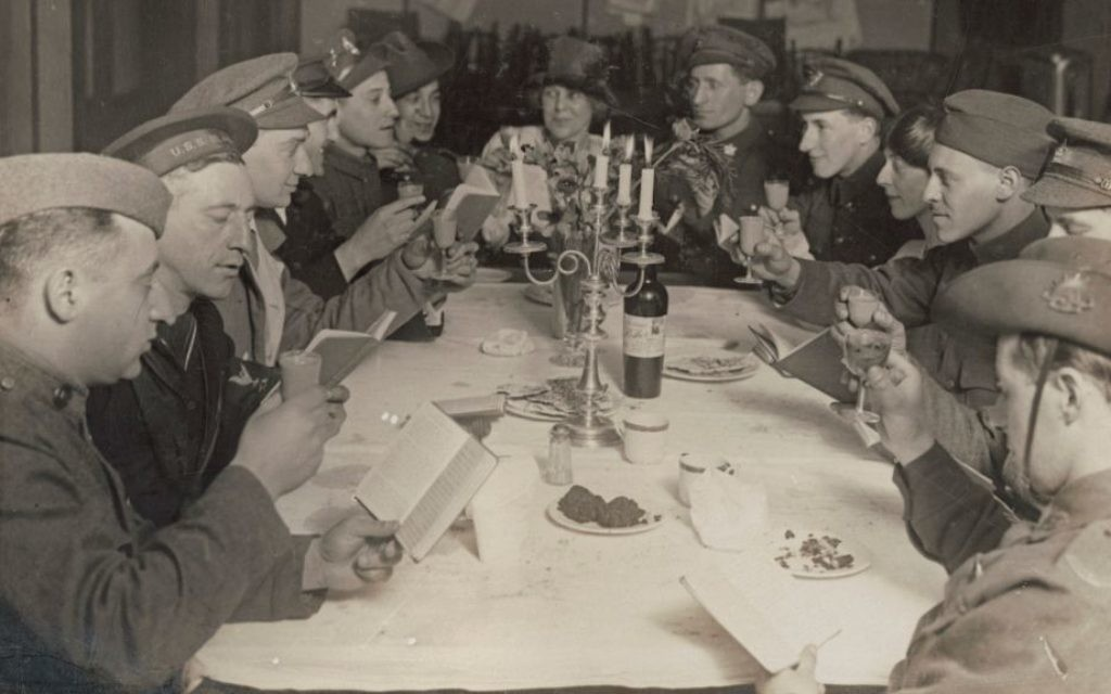 Australian, British and American soldiers and sailors raise their cups at a Passover Seder at the YMCA's Jewish Hut, April 1919. (Courtesy)