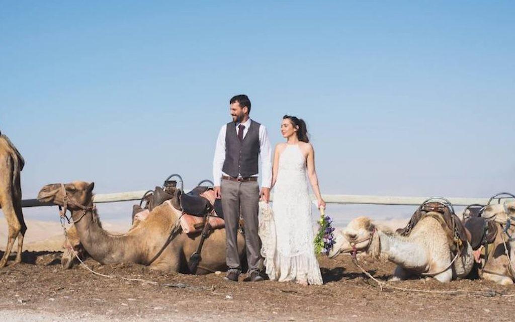 Shani (R) and Ran Maaman enjoy the company of camels at their wedding in the Judean Desert, May 11, 2017. (Dana Bar-On/JTA)