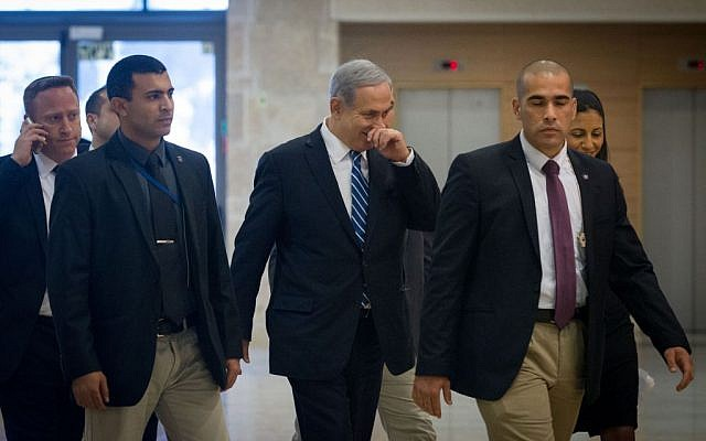 Benjamin Netanyahu, center, arrives to a Likud faction meeting at the Knesset, trailed by aide Ari Harow, far left, on December 8, 2014. (Miriam Alster/Flash90)