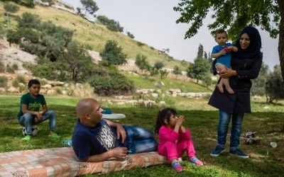 Illustrative: A family enjoys a picnic in the grass, near the East Jerusalem neighborhood of Abu Tur on April 8, 2016.  (Corinna Kern/FLASH90)