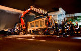 Rescue workers and police at the scene of a pedestrian bridge collapse on a truck on Route 4 near Givat Shmuel, August 14, 2017. (Moti Karelitz/Flash90)