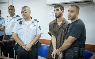 Omar Al-Abed, in handcuffs, is brought to a courtroom for his trial at the Israel's Ofer military court near the West Bank city of Ramallah on August 17, 2017. (Yonatan Sindel/Flash90)