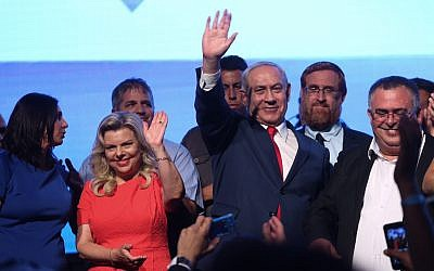 Prime Minister Benjamin Netanyahu and his wife Sara are seen flanked by Likud lawmakers at a Likud party rally in Airport City on August 30, 2017. (Miriam Alster/Flash90)