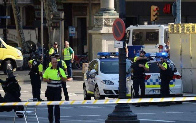 Medical staff members and policemen standing in a cordoned-off area after a van plowed into the crowd on the Las Ramblas Boulevard in Barcelona, Spain, on August 17, 2017. (Josep Lago/AFP/Getty Images)