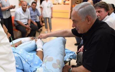 Prime Minister Benjamin Netanyahu visits Yavneh stabbing victim Niv Nehemiah in Kaplan Medical Center, August 8, 2017. (Kobi Gideon/GPO)