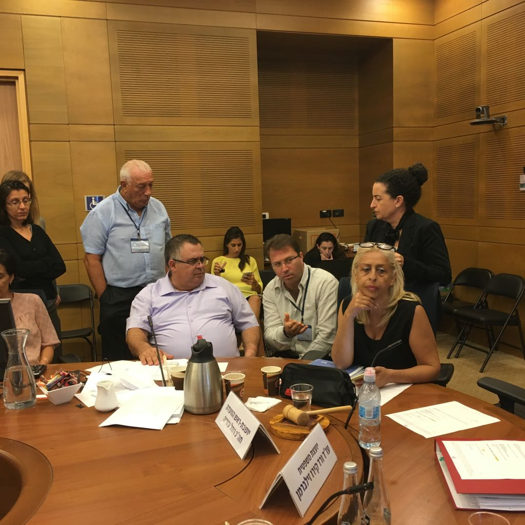 MK David Bitan, seated, with SpotOption's Moshe Avrahami and Knesset Reforms Committee director Ariella Malka, at a Knesset committee meeting to discuss banning Israel's binary options industry, August 7. 2017 (Photo by The Times of Israel)