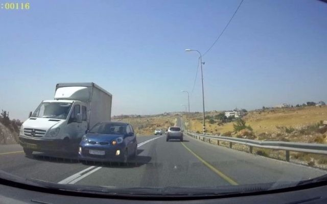 The blue vehicle attempts to pass the white truck by merging into the oncoming traffic lane, nearly colliding with the approaching vehicle on Route 60 in the West Bank. (Courtesy: Avraham Binyamin)