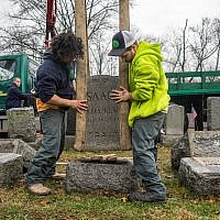 Workers placing headstones back on their bases at Chesed Shel Emeth Cemetery in the St. Louis area. (James Griesedieck)