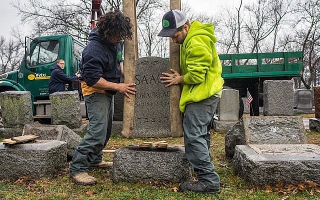 Workers placing headstones back on their bases at Chesed Shel Emeth Cemetery in the St. Louis area. (James Griesedieck via JTA)