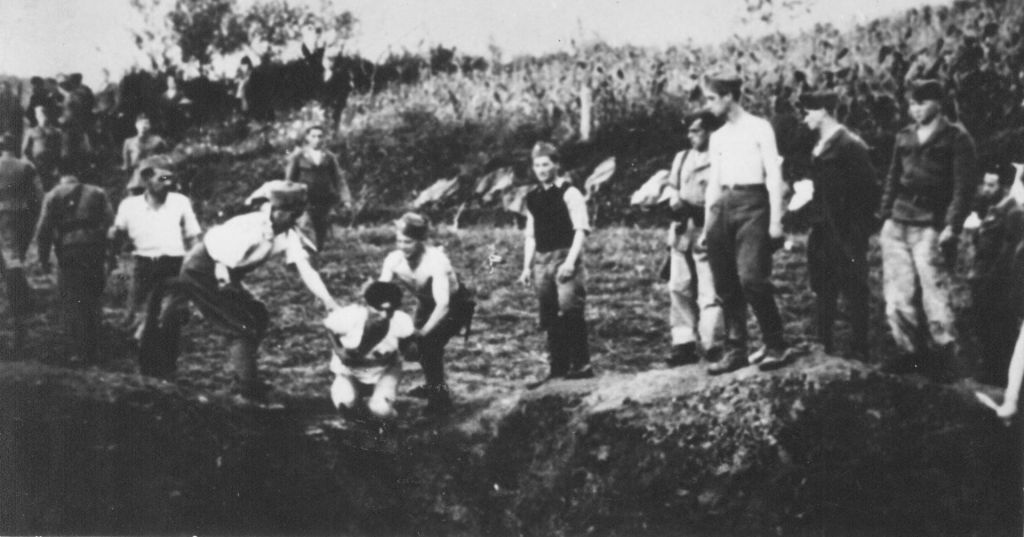 Ustaše militia executing people over a mass grave near Jasenovac concentration camp. (Public domain)