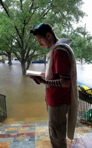Houston B'nai Akiva emissary Rafi Engelhart prays in front of the flooded home in which his family is taking refuge from Tropical Storm Harvey, August 27. (Courtesy)