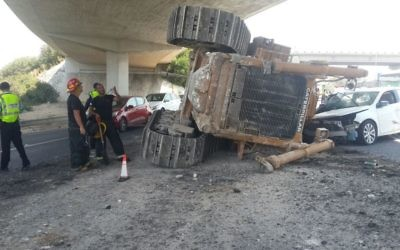 A bulldozer that was knocked off the back of a truck as it passed under a bridge on Route 1, August 21, 2017. (Israel Police)