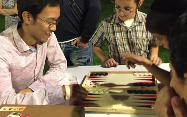 Former World Backgammon Champion Mochy Mochizuki plays against some young Jerusalemites on August 24. (Times of Israel staff)